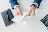 pohled na muže, který drží obálku s penězi blízko notebooku na stole