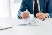 abgeschnittene Ansicht eines Geschäftsmannes, der Stift und Vertrag in der Nähe von Bestechungsgeld auf dem Tisch hält