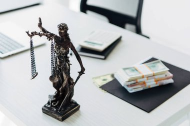 selective focus of statuette of justice near money on wooden table