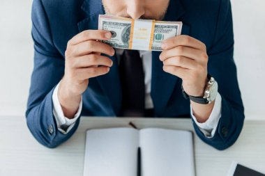 cropped view of businessman smelling dollar banknotes near notebook and pen