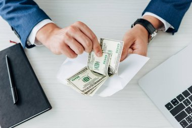 Cropped view of man holding envelope with dollar banknotes near laptop on table stock vector