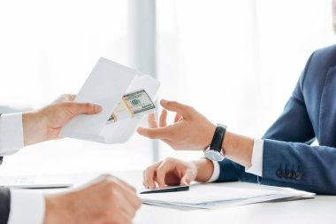 Cropped view of man giving envelope with money to  business partner stock vector