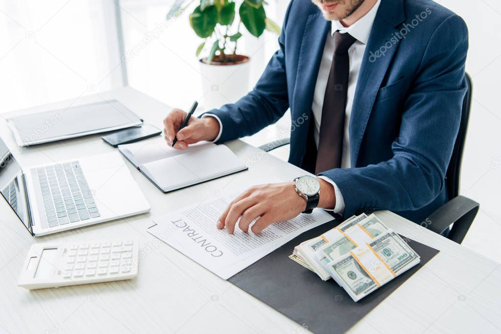 Cropped view of man in suit writing in notebook near money and laptop stock vector
