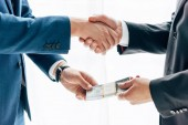 Fotografie cropped view of businessman giving bribe to business partner and shaking hands on white