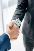 cropped view of man giving bribe to business partner and shaking hands in office