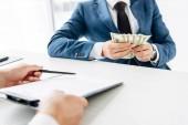 oříznutý pohled muže držící schránku a pero v blízkosti obchodního partnera držby peníze