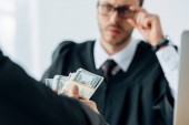 Fotografie selective focus of man holding dollar banknotes near judge in glasses