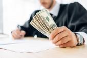 selektivní zaměření soudce, který drží bankovky v dolarech a zapisuje do úřadu