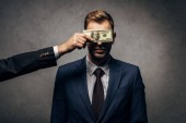 Fotografie cropped view of man covering face of judge with money on black