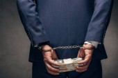 cropped view of handcuffed businessman in suit holding bribe on grey