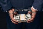 Fotografie close up of handcuffed man in formal wear holding bribe on grey