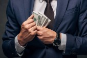 cropped view of businessman in suit putting cash in pocket on grey