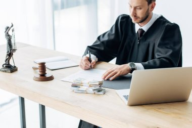 selective focus of laptop near gavel and money near judge and money on table