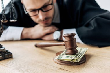 selective focus of wooden gavel on money near judge in glasses