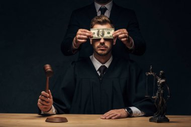 cropped view of man standing and covering face of judge with bribe on black