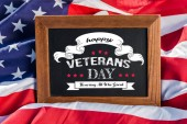 Photo chalkboard with happy veterans day, honoring all who served illustration on american flag with stars and stripes