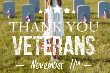 cropped view of kid in white dress standing on graveyard with american flag with thank you veterans illustration