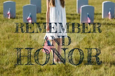 cropped view of kid in white dress standing on graveyard with american flag  with remember and honor illustration