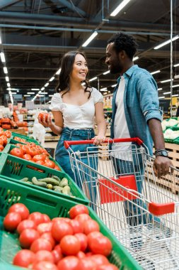 Selective focus of happy asian girl and african american man standing near fresh tomatoes in supermarket stock vector