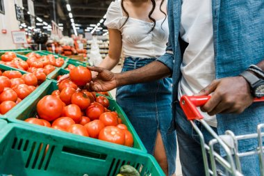 cropped view of african american man holding fresh tomato near girl in supermarket