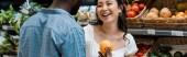 panoramatický záběr šťastné asijské dívky nedaleko afroamerického muže s oranžovým