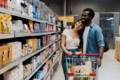 boldog ázsiai nő állandó közelében vidám afro-amerikai barátja, és néztem a polcokon élelmiszerboltok