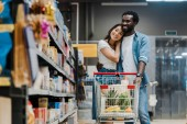 selektivní zaměření veselého afrického amerického muže, který v supermarketu objímá asijskou přítelkyni