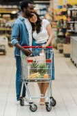 happy asian woman and african american man standing near shopping cart in supermarket