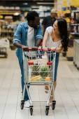 boldog ázsiai nő és afro-amerikai férfi nézi egymást a bevásárlókocsi közelében a szupermarketben