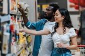 Fotografie selektivní zaměření pohledného afrického Američana ukazováčku s prstem u atraktivní asijské ženy, která se dívá na police s potravinami