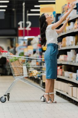 happy young asian woman standing near shelves with groceries and shopping cart in supermarket