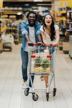 Happy interracial couple smiling while running while shopping cart in supermarket stock vector