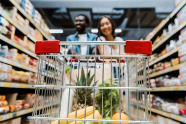 selective focus of fruits in shopping cart near happy interracial couple in store