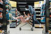 boldog afro-amerikai férfi nézi ázsiai lány ül a bevásárlókosárba, és intés a szupermarketben