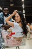 szelektív középpontjában ázsiai lány ül a bevásárlókosárban közel szép afro-amerikai ember