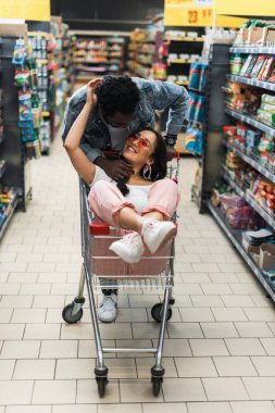 selective focus of cheerful african american man looking at asian woman in sunglasses holding bottle and sitting in shopping cart