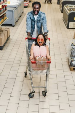 happy african american man walking with asian girl in sunglasses sitting in shopping cart