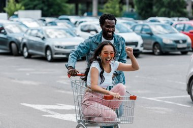 happy asian girl gesturing while sitting in shopping trolley near african american man and cars