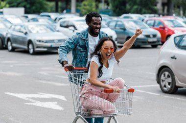 stylish asian girl gesturing while sitting in shopping trolley near african american man and cars