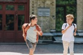 two cute schoolboys running in schoolyard while smiling and looking at each other