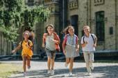 vier glückliche multiethnische Schulkinder lächeln beim Laufen auf dem Schulhof