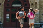Rückansicht von zwei Schulkindern mit Rucksäcken auf dem Schulhof
