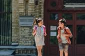 fröhliche Schülerin und Schülerin lächelnd und schaueneinander beim Laufen auf dem Schulhof