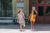 zwei fröhliche multiethnische Schülerinnen lächeln beim Laufen auf dem Schulhof