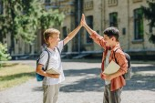 two cheerful schoolboys giving high five while standing in schoolyard