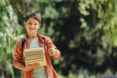 Veselý školák s úsměvem na kameře a s palcem nahoru a přidržující knihy