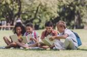 čtyři rozkošní multikulturní studenti, kteří sedí na trávníku a čtou knihy