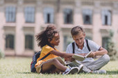 two adorable multicultural schoolkids sitting on lawn and reading books together