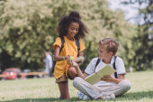 cute schoolboy sitting on lawn and giving apple to smiling african american schoolgirl