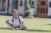 adorable schoolboy sitting on lawn near school and reading book